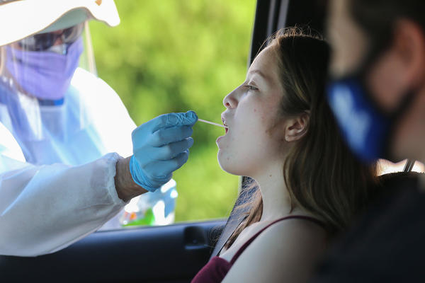 A health care worker administers a throat swab test at a drive-in COVID-19 testing center.
