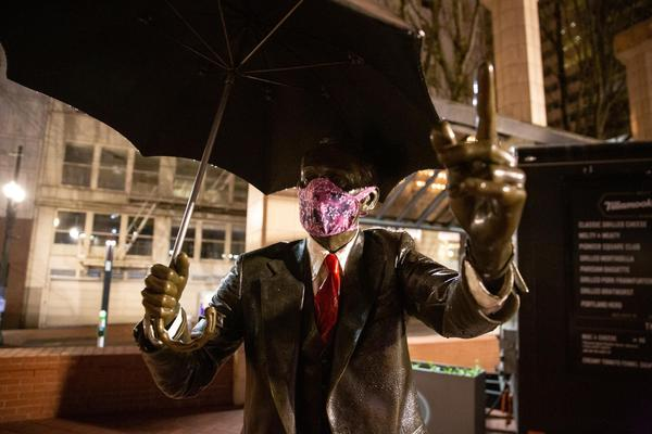 The Umbrella Man statue wears a mask in Pioneer Courthouse Square in Portland, Ore., Saturday, April 18, 2020.