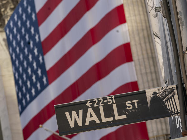 The Wall Street sign is shown framed by the American flag hanging on the New York Stock Exchange, on Sept. 21, 2020. Stocks posted their best weekly gain since April despite an uncertain election.