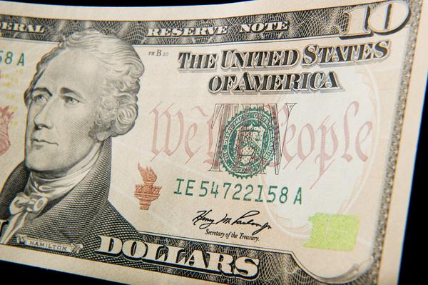 A close-up of the front of the US 10-dollar bill bearing the portrait of Alexander Hamilton, America's first Treasury Secretary.