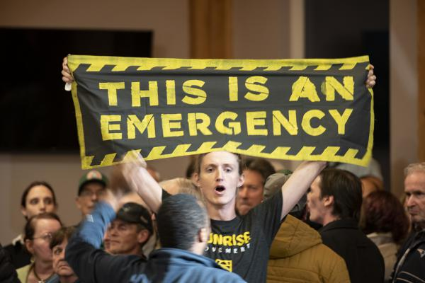 """A climate change protester holds a banner reading, """"This Is An Emergency,"""" during a 2019 town hall event in Manchester, N.H., with Joe Biden, who isn't pictured."""
