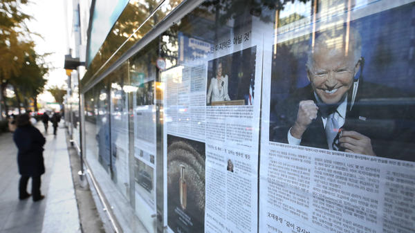 A newspaper's front page featuring President-elect Joe Biden and Vice President-elect Kamala Harris is displayed on a sidewalk in Seoul, South Korea, on Monday.