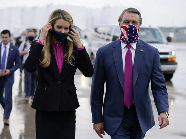 Sen. Kelly Loeffler, R-Ga., puts on a face mask as she walks with Sen. David Perdue, R-Ga., in July in Atlanta.