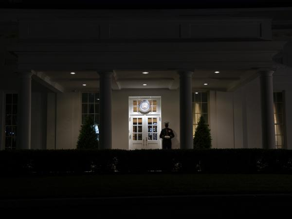 A Marine stands outside the entrance to the West Wing of the White House on Tuesday, signifying that President Trump is in the Oval Office.