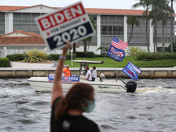 A person shows her support for Joe Biden as boaters pass by showing their support for President Donald Trump during a parade down the Intracoastal Waterway on Oct. 3, 2020 in Fort Lauderdale.