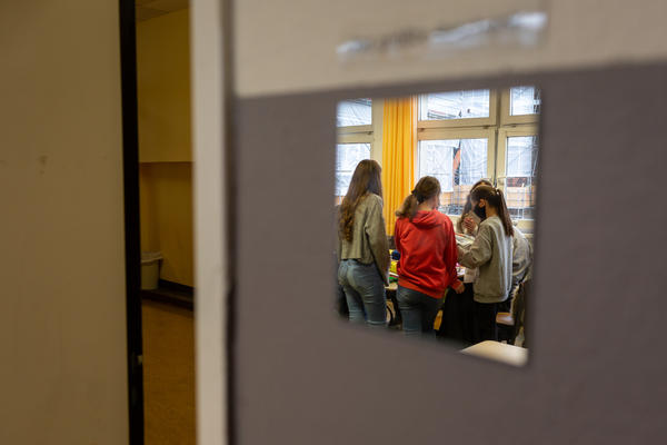 Students working on a book project at the Fritz-Karsen-Shule in Berlin are reflected in a mirror on the classroom wall.