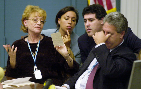 Palm Beach County canvassing board chairman Judge Charles Burton rubs his eyes as board member Carol Roberts (left) shows a questionable ballot to the Democratic attorneys during the hand counting of ballots in West Palm Beach, Fla., on Nov. 22, 2000.