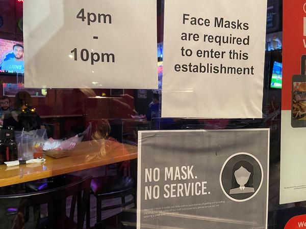 A bar in Cleveland with a sign showing masks are required to enter.
