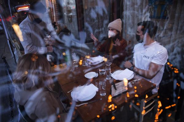 Server Luis Velez opens a bottle of wine for customers Mary Graf, left, Sophie Mandel and Andy Peraza, right, shown through a sheet of plastic surrounding the table, on Wednesday, October 21 , 2020, at Spinasse on Capitol Hill in Seattle.