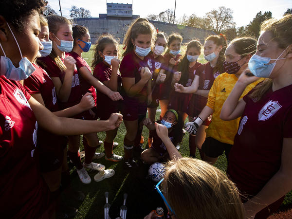 The Lowell High School girls soccer team fist bumps before a game this month in Massachusetts. The coronavirus pandemic has curtailed youth athletics leaving some students scrambling for opportunities.