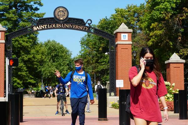 St. Louis University students walk across the crosswalk on Father Biondi SJ Way on Monday, Aug. 17.