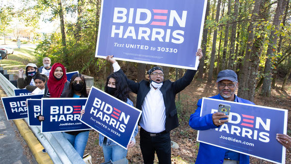 Residents of Gwinnett County in Georgia hold Biden-Harris campaign signs on Election Day in Norcross, Ga. President-elect Joe Biden ran up the margins in Atlanta's diversifying suburbs.