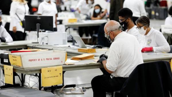 Election workers count absentee ballots earlier this month in Detroit, the county seat of Wayne County, Mich.