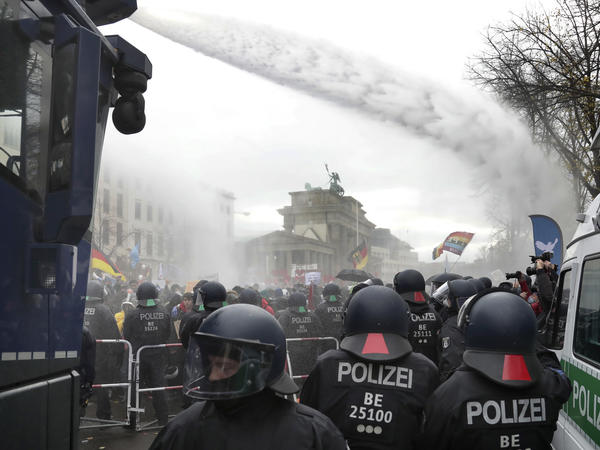 Police use water cannons to clear a road between the Brandenburg Gate and the Reichstag, home of the German parliament, as people attend a protest rally Wednesday in Berlin.