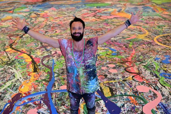 """Artist Sacha Jafri, standing on his gigantic painting entitled """"The Journey of Humanity,"""" hopes to raise $30 million to fund health and education initiatives for children living in poverty worldwide."""