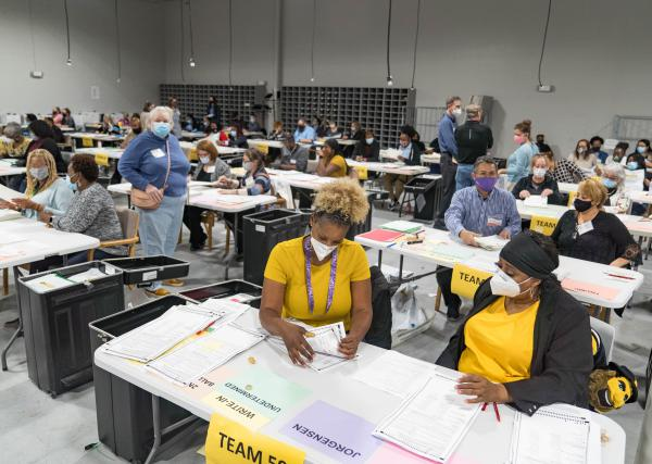 Gwinnett County election workers handle ballots Monday in Lawrenceville, Ga., as part of the state's recount for the 2020 presidential election.