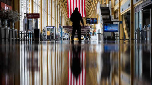 An airport employee walks through Reagan National Airport in Arlington, Va., earlier this year. On Thursday, the Centers for Disease Control and Prevention warned that Americans should refrain from traveling for the upcoming holiday.