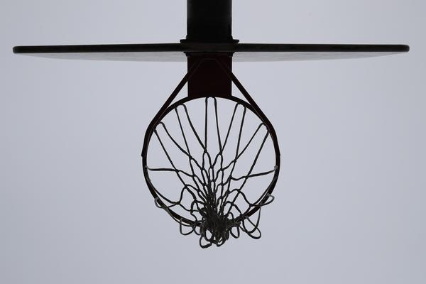 A basket in Cartwright park is zip tied closed to prevent people from playing basketball on closed courts in Evanston, Ill., Friday, March 27, 2020.