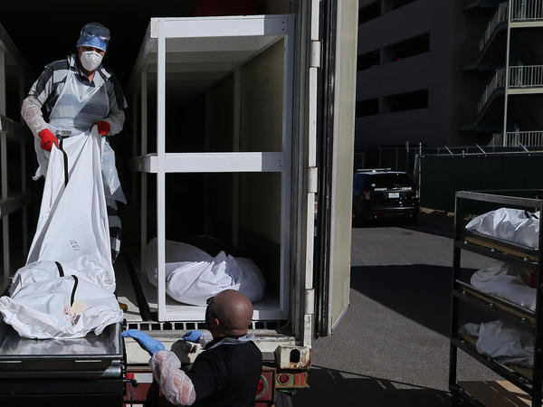 A low-level inmate from El Paso County detention facility works loading bodies wrapped in plastic into a refrigerated temporary morgue trailer in a parking lot of the El Paso County Medical Examiner's office on Tuesday.