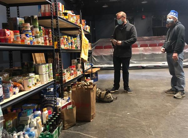 Actors Jake Walker and J. Will Fritz check out the inventory in the Theatre Community Fund of Kansas City's food bank, currently housed inside the Unicorn Theatre's Jerome Stage.