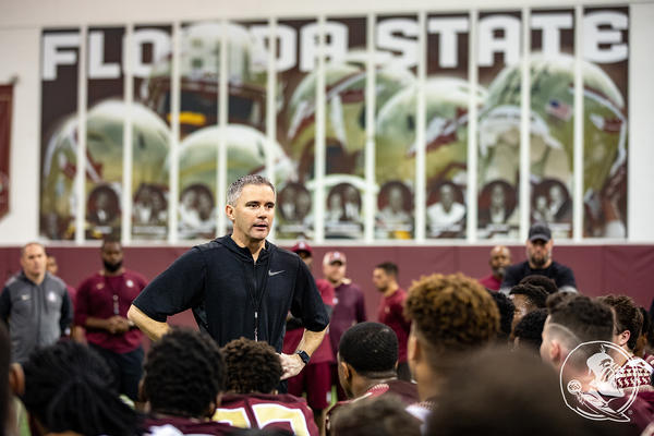FSU head football coach speaks with players during a pre-season workout