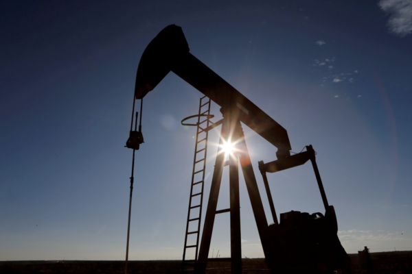 The sun is seen behind a crude oil pump jack in the Permian Basin in Loving County, Texas, on November 22, 2019.