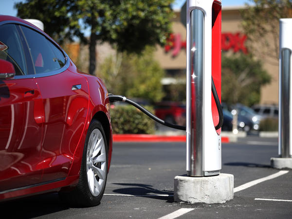 A Tesla car powers up at a charging station in Petaluma, Calif., on Sept. 23. Automakers are trying to convince would-be electric car buyers to adopt new habits to power their vehicles.