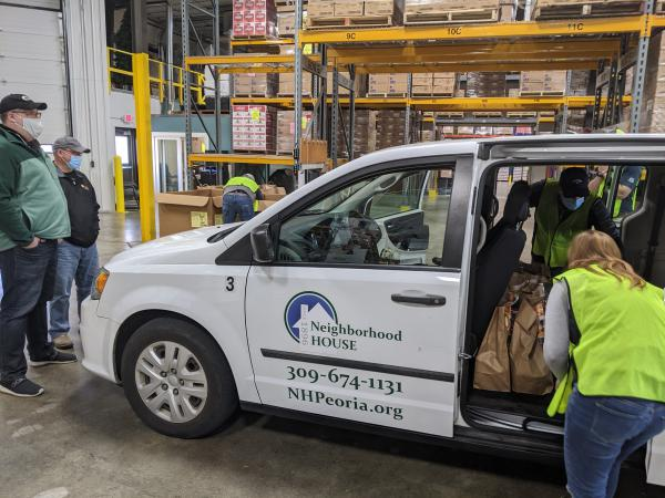 Volunteers load Thanksgiving meal kit donations from Hy-Vee into a Neighborhood House van at the Midwest Food Bank facility in North Peoria.