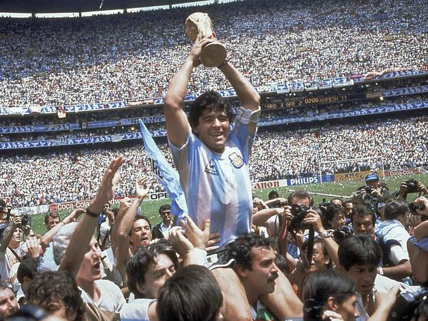 Diego Maradona holds up his team's trophy after Argentina's 3-2 victory over West Germany at the World Cup final soccer match at Azteca Stadium in Mexico City in 1986. The Argentine soccer great who was among the best players ever, died from a heart attack on Wednesday.