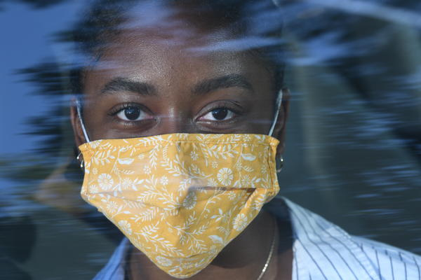 A woman wears a cloth mask, as recommended by the CDC and World Health Organization to slow the spread of COVID-19. Photo illustration.