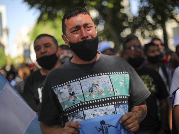 A man cries as he waits in a line outside the presidential palace to pay his final respects to Diego Maradona, in Buenos Aires on Thursday.