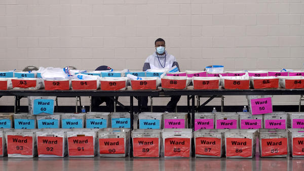 An election official pauses during the ballot recount earlier this month at the Wisconsin Center in Milwaukee. After recounts in Milwaukee and Dane counties, President-elect Joe Biden narrowly increased his winning margin over President Trump.
