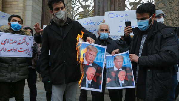 Iranian protesters burn images of President Trump and President-elect Joe Biden during a rally Saturday in  Tehran. Iranian leaders have blamed Israel and its close ally, the U.S., for the assassination of a top Iranian nuclear scientist.