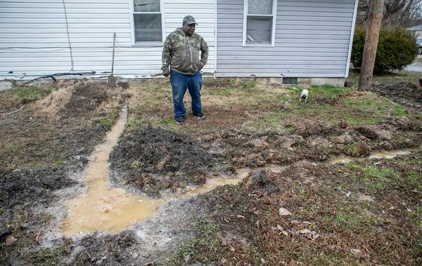 Centreville resident Walter Byrd stands in his side yard next to raw sewage and his attempt to keep the sewage from backing up into his home.