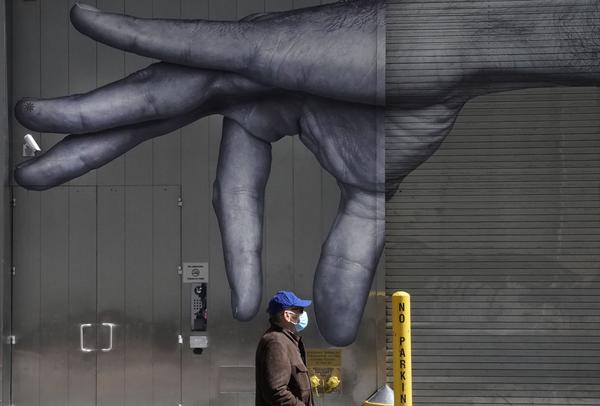 A man in a mask walks past a mural on the side of a building in New York City in April.