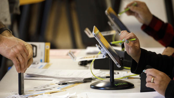 An election worker uses an electronic pollbook to check voters at a polling station in the Echo Park Recreation Complex in Los Angeles on March 3, 2020.