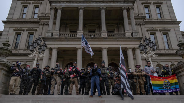 "Far-right extremist ""Boogaloo boys"" stand on the steps of the capitol in Lansing, Mich., during a rally on Oct. 17. Michigan is one of five states with the highest risk of increased militia activity around the elections, according to a new report."