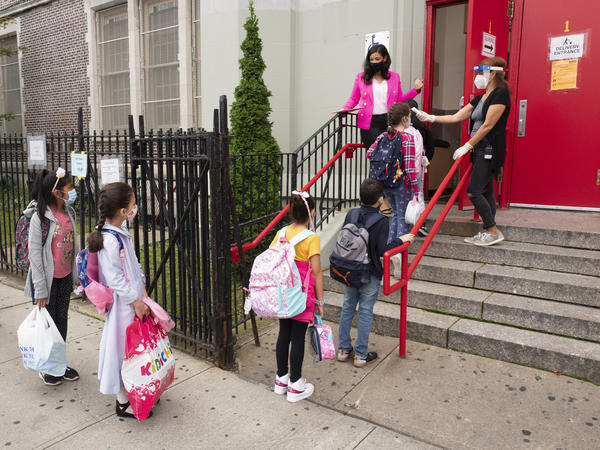 Students line up outside P.S. 179 in the Kensington section of Brooklyn, in New York City, to have their temperatures checked on the first day of in-person instruction, on Sept. 29. This Thursday, New York City public schools will be halting in-person instruction.