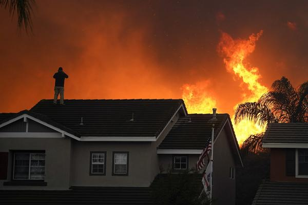 Herman Termeer, 54, stands on the roof of his home as the Blue Ridge Fire burns along the hillside Tuesday, Oct. 27, 2020, in Chino Hills, Calif.