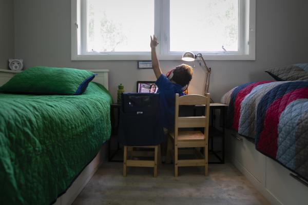 A student raises his hand while attending an online class from home in Miami on Sept. 3.