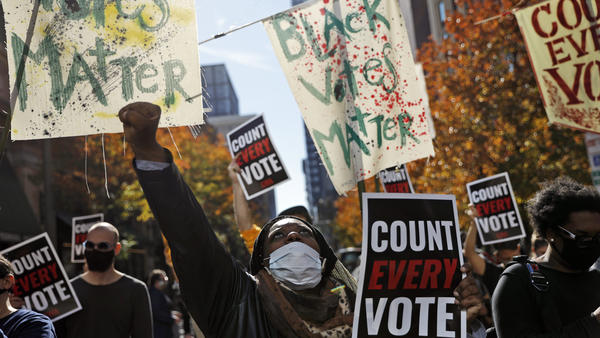 Zhanon Morales, 30, of Philadelphia raises a fist during a Nov. 5 voting rights rally. President Trump's campaign unsuccessfully used spurious claims of voter fraud to invalidate votes in Philadelphia and other largely Black cities.