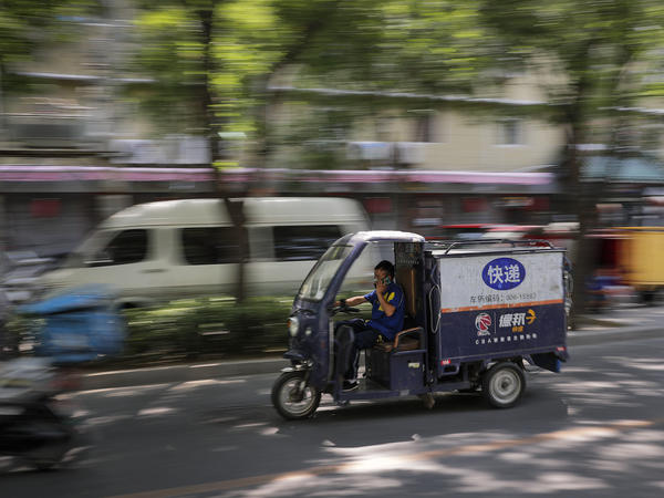 A private delivery company's courier drives his delivery vehicle in a residential area in Beijing in June.