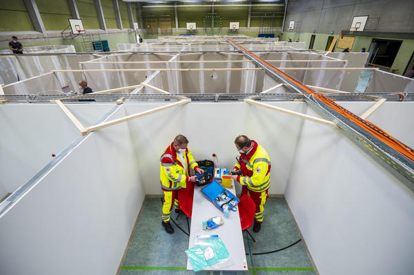 "The pending arrival of vaccines has brought ""hope for a brighter future,"" the OECD says. Here, workers from the Red Cross and the Federal Agency for Technical Relief help set up a center for COVID-19 vaccinations in a gymnasium in Eschwege, Germany."