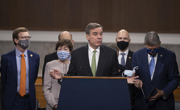 Sen. Mark Warner speaks alongside a bipartisan group of lawmakers as they announce a proposal for a $908 billion coronavirus relief bill on Tuesday.