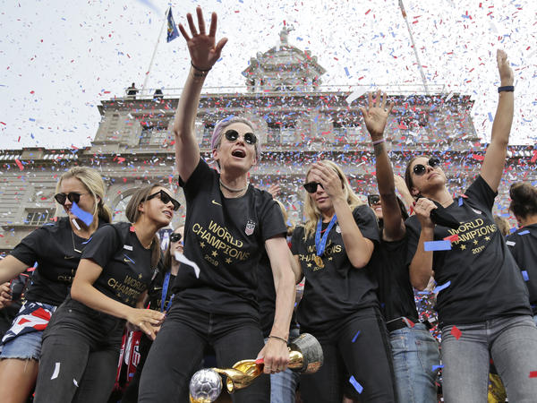 """Megan Rapinoe (center) and Alex Morgan (right), pictured celebrating with U.S. women's soccer teammates in New York after a ticker tape parade, on July 10, 2019. """"We are pleased that the USWNT Players have fought for – and achieved – long overdue equal working conditions,"""" a spokeswoman for the team said on Tuesday."""
