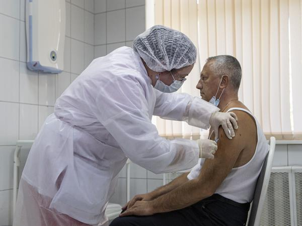 A Moscow health care worker administers a shot of Russia's Sputnik V coronavirus vaccine during clinical trials in September. President Vladimir Putin ordered the nation's health authorities to begin mass vaccinations next week.