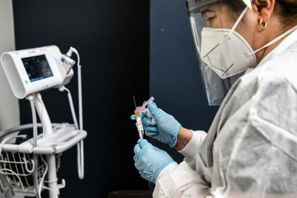 Yaquelin De La Cruz holds a COVID-19 vaccine during clinical trials in August at the Research Centers of America in Hollywood, Fla.