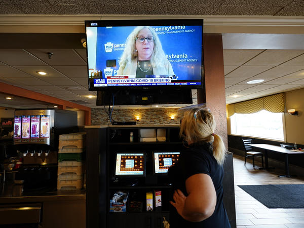 """A waitress in South Philadelphia watches a television briefing by Pennsylvania's health secretary, Dr. Rachel Levine, on Nov. 17. Levine says a COVID-19 vaccine is """"the light at the end of the tunnel,"""" but says it will be months before it's available to the general public."""