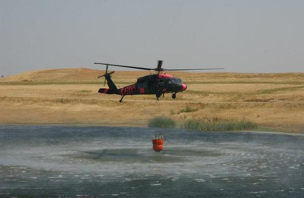Kansas National Guard troops use a helicopter bucket to fight wildfires in November. This year state National Guards have faced unprecedented duties as they have dealt with natural disasters, overseas deployments and the pandemic.