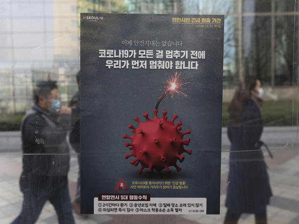 People wearing face masks as a precaution against the coronavirus pass by a poster emphasizing an enhanced social distancing campaign at a bus station on Monday in Seoul.